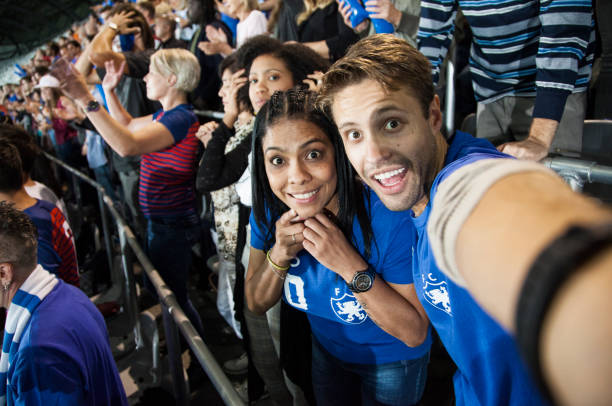 young couple at footbal match making a selfie - concert selfie stock photos and pictures