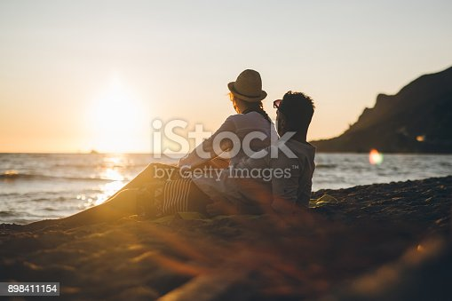 Young modern couple at beach enjoying in sunset by the sea