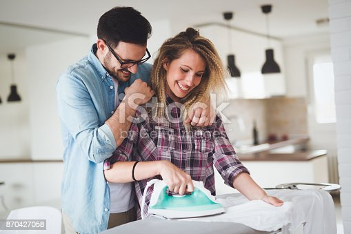 802472024istockphoto Young couple at home doing hosehold chores and ironing 870427058