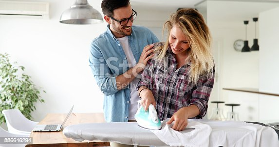 802472024 istock photo Young couple at home doing hosehold chores and ironing 886646294