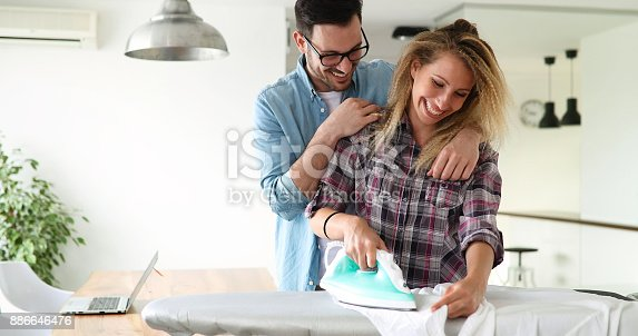 802472024 istock photo Young couple at home doing hosehold chores and ironing 886646476