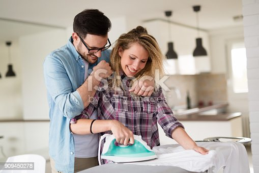 802472024 istock photo Young couple at home doing hosehold chores and ironing 909450278