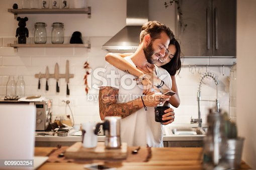 istock Young couple at home using smartphone - Morning breakfast time 609903254
