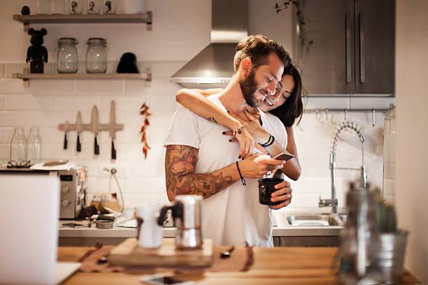 junges paar zu hause mit dem smartphone - morgenfrühstück - junges paar stock-fotos und bilder