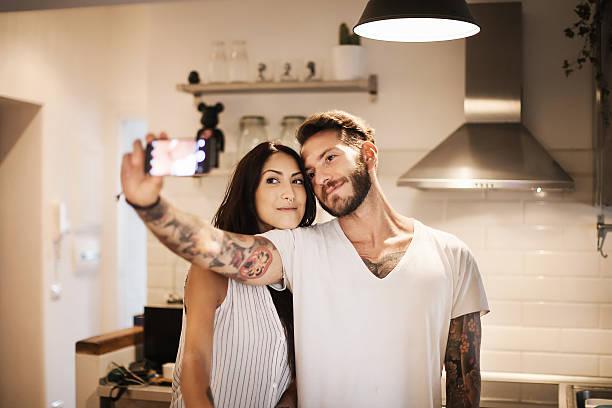 young couple at new home - selfie - ehepaar tattoos stock-fotos und bilder