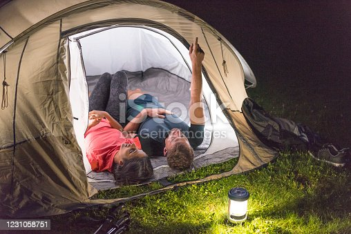 Young couple at night lying in their tent and talking