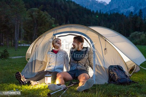 Young couple at night sitting and talking in front of their tent