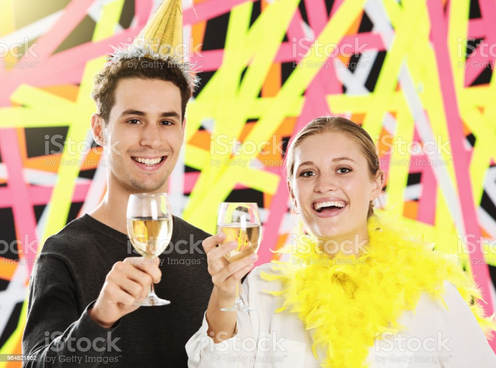 Young couple at party lift glasses to camera in toast royalty-free stock photo