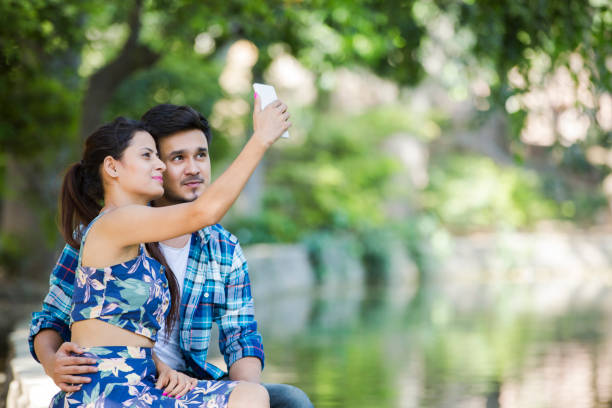 Young couple at public park - stock images India, Delhi, Young Couple, Modern, Lifestyle, Outdoors, romance stock pictures, royalty-free photos & images