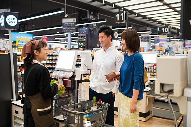 young couple at the checkout - 小売販売員 ストックフォトと画像