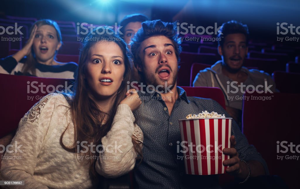 Young couple at the cinema watching an horror movie stock photo