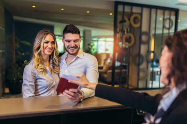 Young couple at the hotel reception Young couple at the hotel reception inn stock pictures, royalty-free photos & images