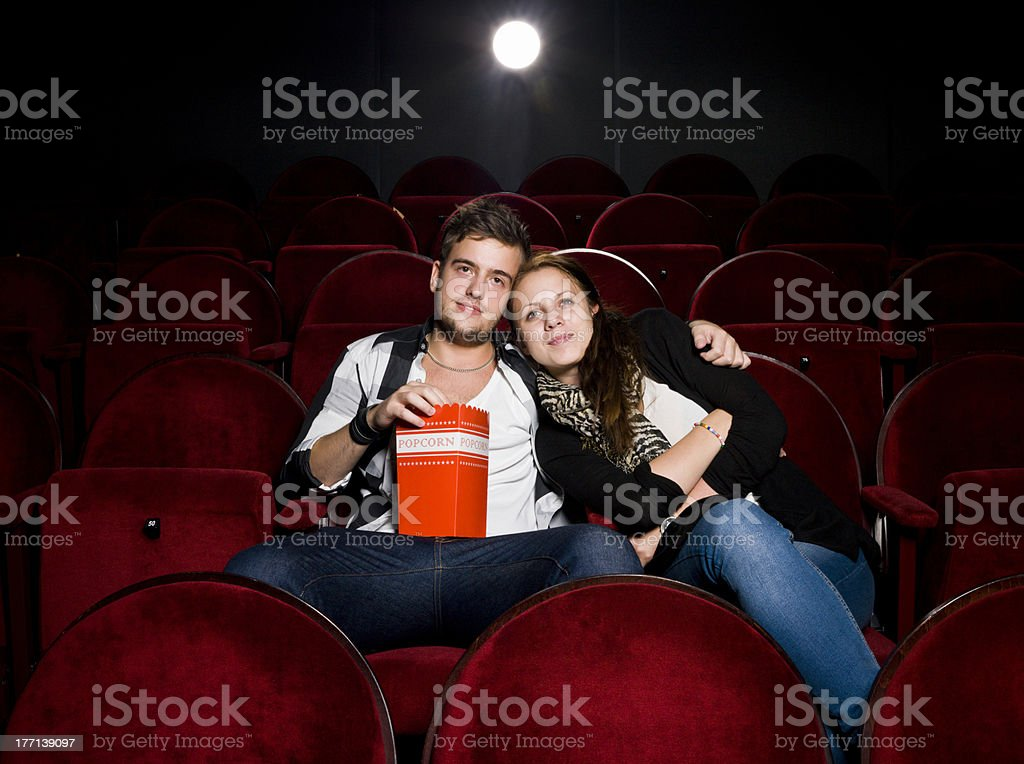 Young couple at the movies enjoying popcorn stock photo