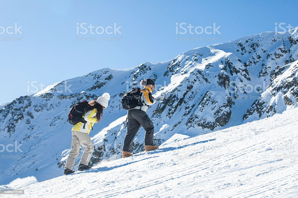Young couple backpackers moving up on snow mountain royalty-free stock photo