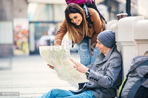 istock Young Couple Backpackers Sitting On The Stairs Of City Fontain 672022720