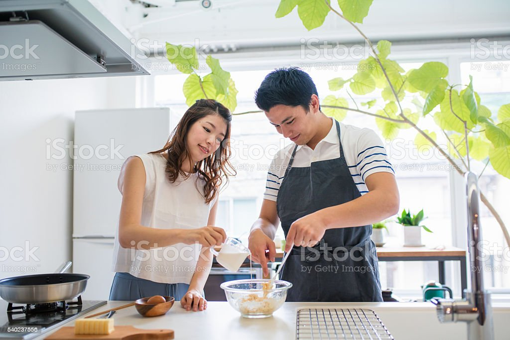 Young couple baking together in the kitchen stock photo