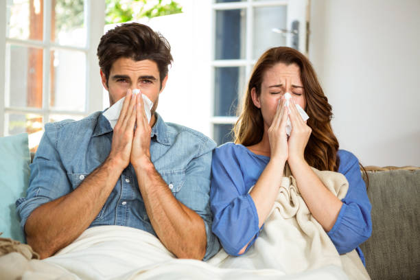 Young couple blowing their nose in tissue stock photo