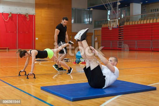 Young Couple Body Workout With Male Trainer Indoors Gym Stock Photo & More Pictures of 25-29 Years