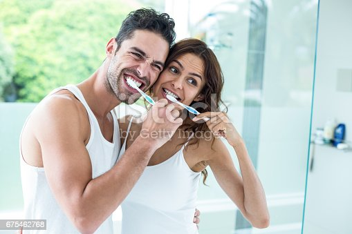 675462768istockphoto Young couple brushing teeth while standing in bathroom 675462768