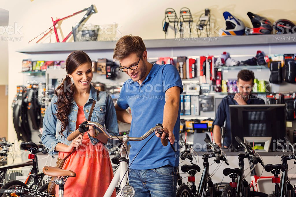Young couple buying a bicycle Young couple watching a bicycle in a bike store with sales assistand standing in the background. 20-24 Years Stock Photo