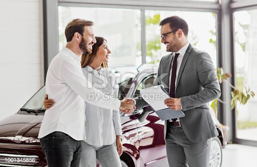 988321834 istock photo Young couple buying a car in auto salon 1001345856