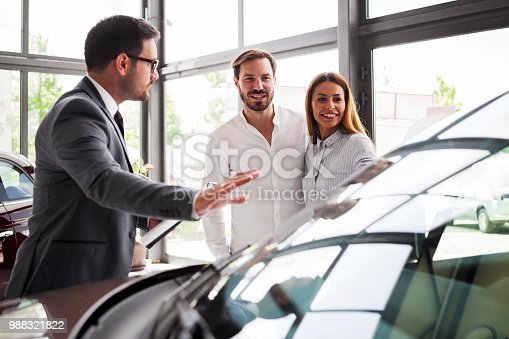 988321834 istock photo Young couple buying a car in auto salon 988321822