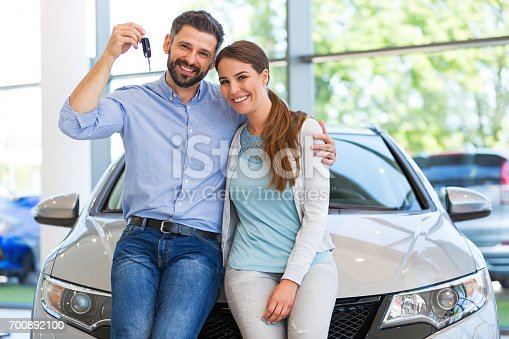istock Young couple buying a car 700892100
