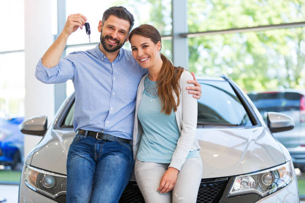 Young couple buying a car Young couple in the showroom, choosing a car car stock pictures, royalty-free photos & images