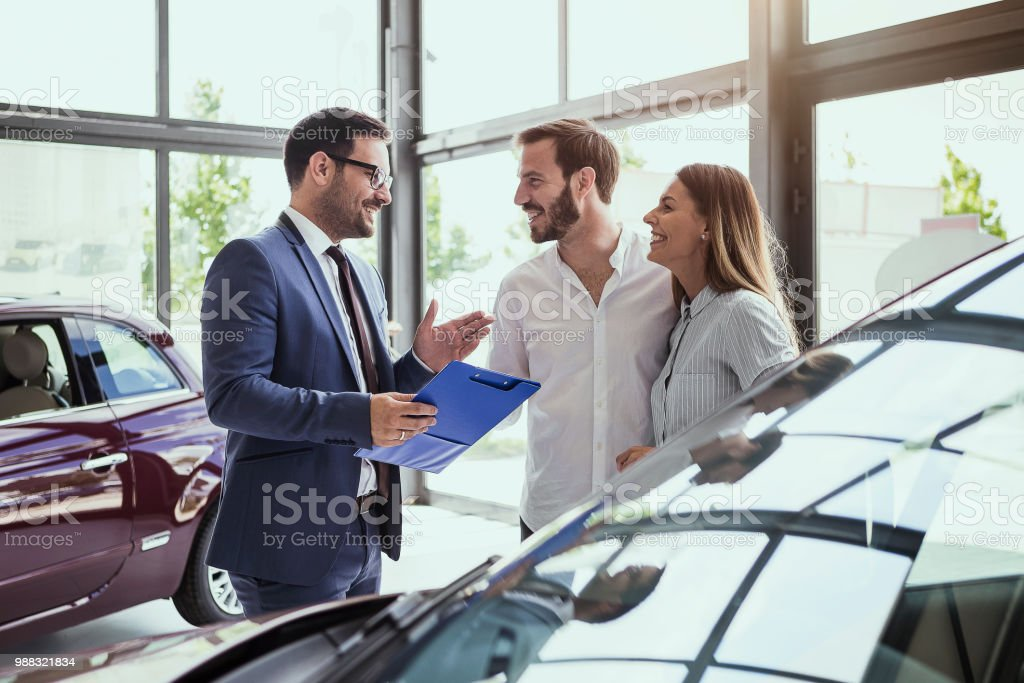 Young couple buying a car Car salesman making a sale Adult Stock Photo
