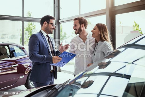 istock Young couple buying a car 988321834