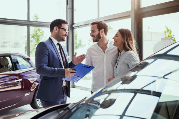 young couple buying a car - selling stock pictures, royalty-free photos & images
