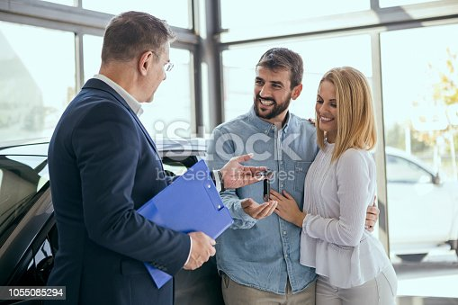 988321834 istock photo Young couple buying a car ,taking keys 1055085294