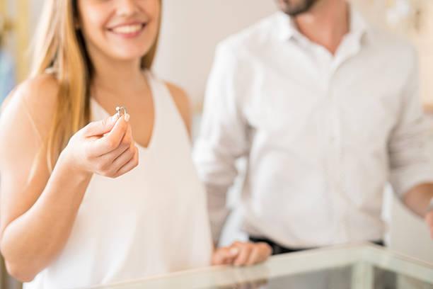 young couple buying a diamond ring - diamanten kaufen stock-fotos und bilder