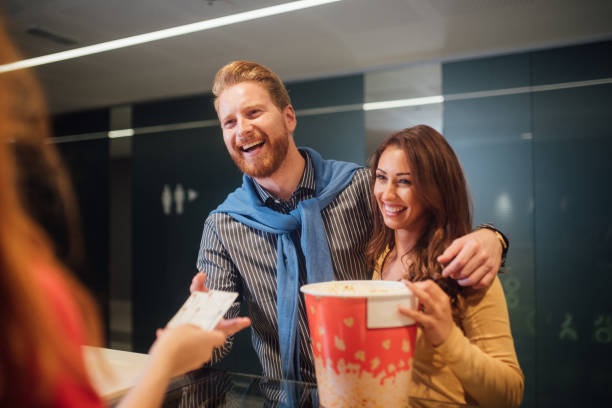 Young couple buying movie tickets Happy young couple buying popcorn and movie tickets at cinema admit stock pictures, royalty-free photos & images