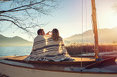 Cheerful young couple wrapped in blanket by the lakeshore watching the sunset and making a heart shape finger frame, beautiful Autumn sunlight.