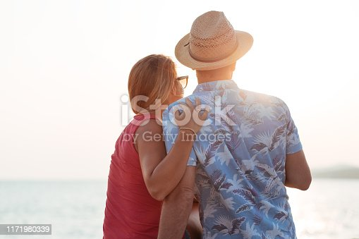 492610640istockphoto Young couple by the sea looking into the sun 1171980339