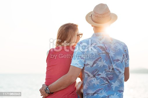 492610640istockphoto Young couple by the sea looking into the sun 1171980343