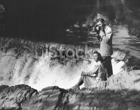 istock Young couple by waterfall, man taking picture, (B&W) 57416962