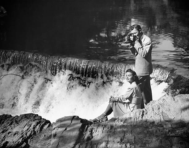 Young couple by waterfall, man taking picture, (B&W) stock photo
