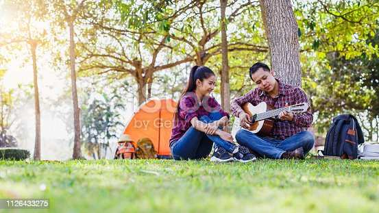 627343204 istock photo Young couple camping enjoying playing guitar and sitting at outside camping tent, Couple camping concept 1126433275
