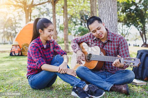 627343204 istock photo Young couple camping enjoying playing guitar and sitting at outside camping tent, Couple camping concept 1126436388