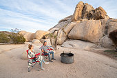 Young couple camping in nature near boulders at sunset; two people with camping chairs near bonfire enjoying the evening vacations