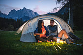 Relaxed camping couple in 20s and 30s sitting on tent porch and talking at dusk with Julian Alps in background.