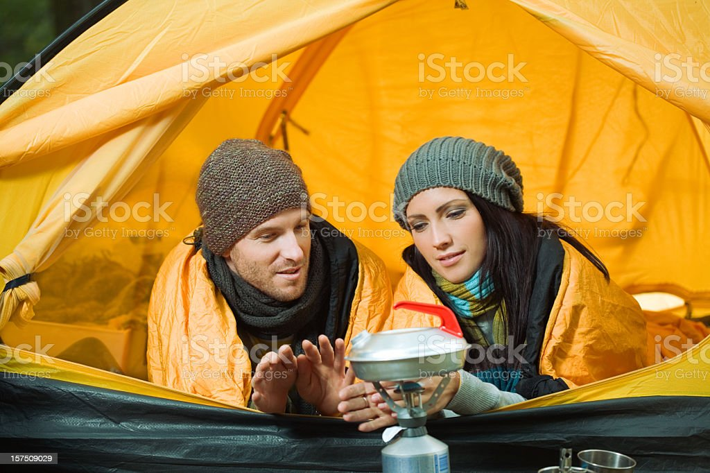Young Couple Camping, Warming Up Hands royalty-free stock photo