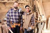 Young couple carpenters in workshop. Both with safety goggles and work clothes, tools and gloves.