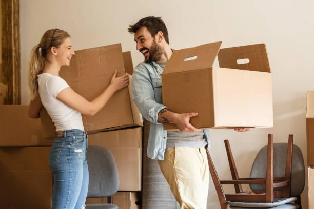 ungt par som transporterar stor pappkartong till nytt hem. flytt huset. - flyttlådor bildbanksfoton och bilder