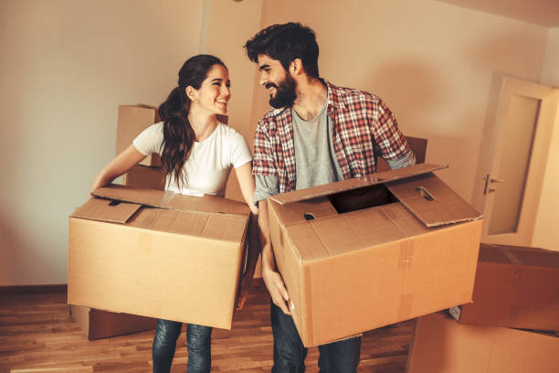 Young couple carrying big cardboard into a new home.Moving house.Real estate concept. stock photo