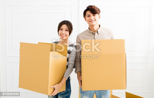 istock young Couple Carrying Boxes Into New Home 875592640