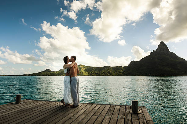 Young Couple Celebrating a Polynesian Wedding in Bora Bora A DSLR photo of a newlywed couple kissing in wood pier over the wonderful sea of Bora Bora, French Polynesia. It is just after sunset, so all scene is very soft lit. She is wearing a white wedding dress. In the background, silhouetted against the sky, is mountain Otemanu, main natural landmark in Bora Bora. indo pacific ocean stock pictures, royalty-free photos & images