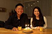 フルーツケーキで誕生日を祝う若いカップル